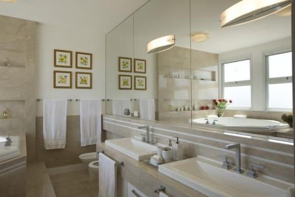 Banheiro de casal com espelho grande e bancada clara (foto: Jannini Sagarra Arquitetura)