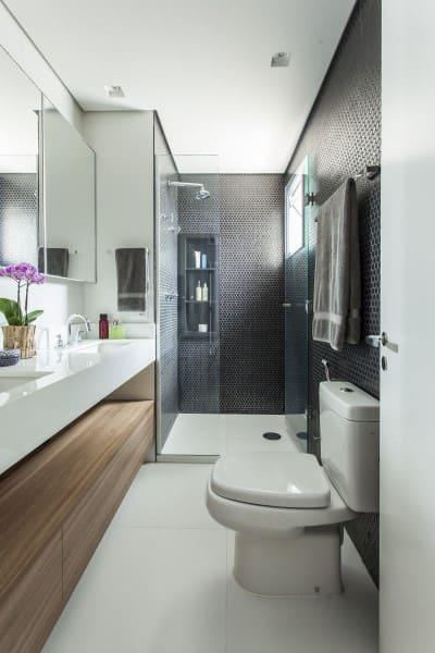 Banheiro de casal com gabinete amadeirado e revestimento hexagonal preto (foto: Karina Korn)