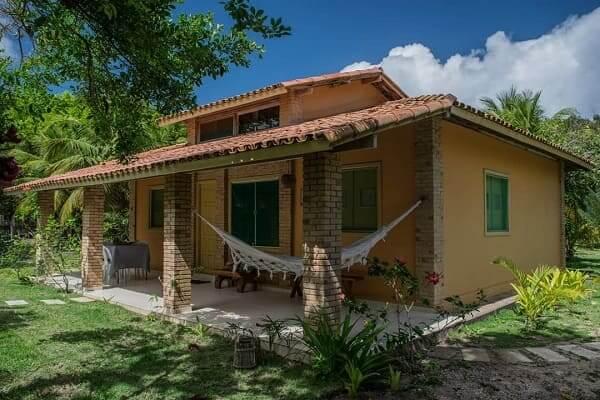 Projeto de Casa de Praia: casa com telhado de duas águas e fachada de tom neutro (fonte: @sitiocantodosabia)
