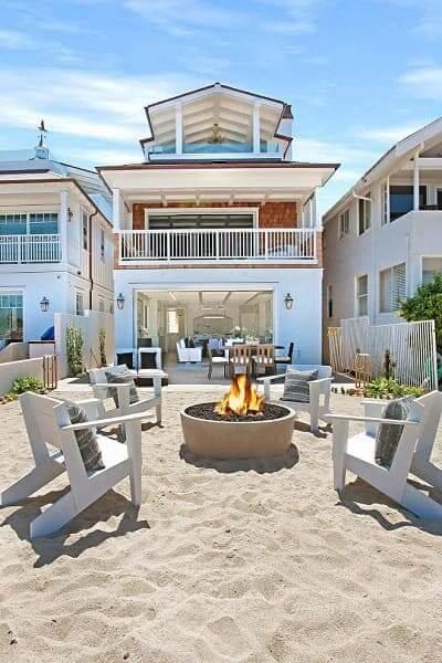 Projeto de Casa de Praia com fachada branca e lareira a área externa