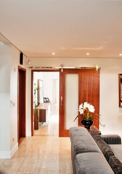 Tipos de portas: porta de correr de madeira com detalhe branco (projeto: Archdesign Studio)