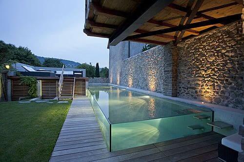 Piscina de Vidro com parede de pedras traz o aconchego da natureza (foto: decorando casas)