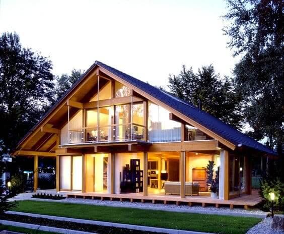 Fachadas de casas térreas com telhado de duas águas: chalé de madeira com fachada de vidro tem integração com a natureza
