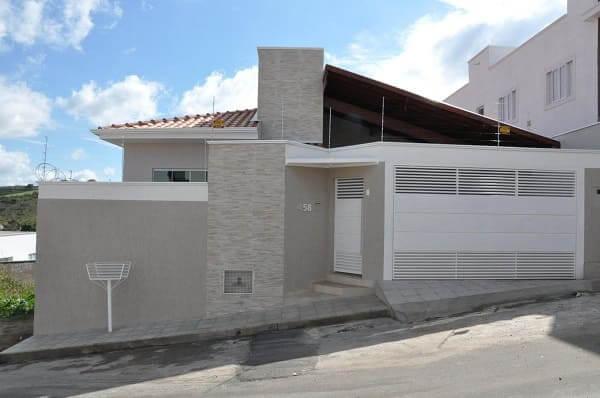 Fachadas de casas térreas: portão branco com parede de pedra (projeto: Cláudia Breias)