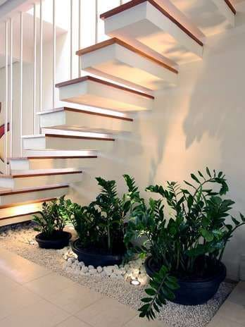 Jardim de inverno embaixo da escada: vasos cerâmicos pretos e piso com pedras brancas (fonte Revista Viva Decora)