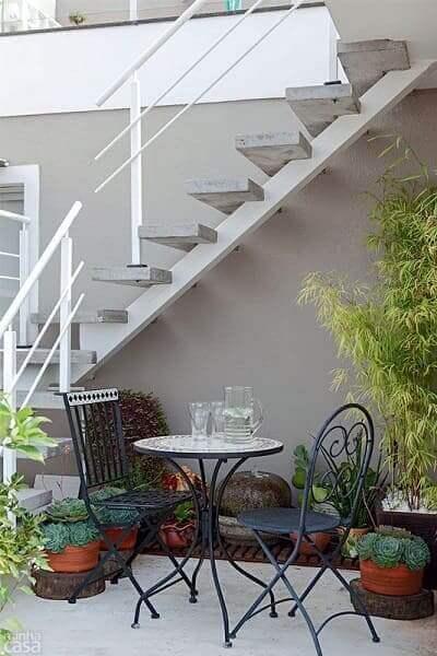 Jardim embaixo da escada externa: mesa e cadeira criam um espaço para receber visitas
