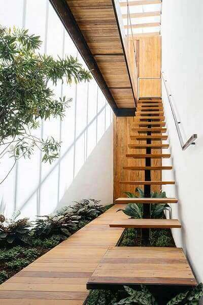Jardim embaixo da escada externa: plantas em verde escuro combinam com madeira