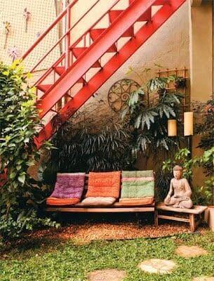 Jardim embaixo da escada externa: sofá e decoração deixa ambiente relaxante