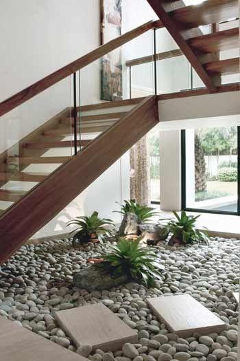 Jardim embaixo da escada: plantas baixas e pedras combinam com escada de madeira