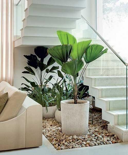Jardim embaixo da escada: vasos grandes e pedregulhos criam ambiente elegante