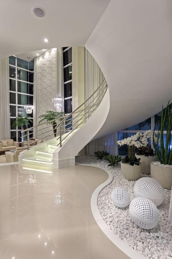 Jardim embaixo da escada: vasos de cor creme e esferas vazadas dão charme à escada (Projeto: Aquiles Nícolas Kílares)