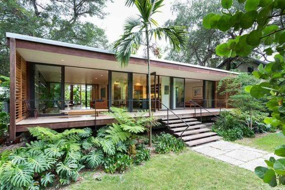 Fachadas de casas térreas: fachada de vidro traz integração com a natureza