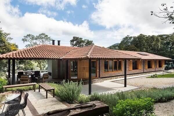 Fachadas de casas térreas com telhado aparente: tijolinhos e madeira compõem fachada rústica (projeto: RAP Arquitetura e Interiores)