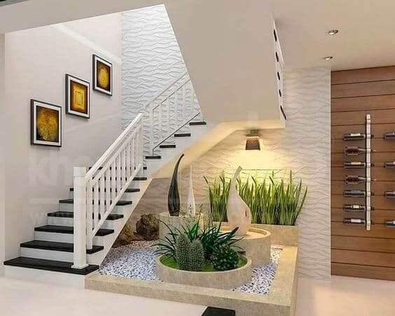 Jardim de inverno embaixo da escada: vasos grandes e esculturas transforma espaço