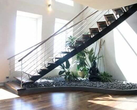 Jardim embaixo da escada: escultura e pedras cinzas combinam com a escada