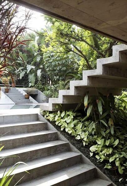 Jardim embaixo da escada externa: verde cria linda combinação com cimento queimado