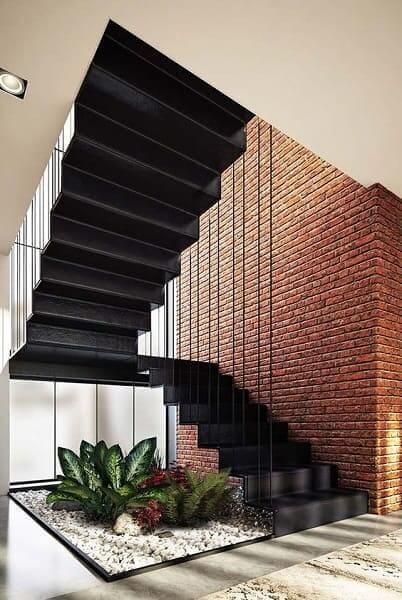 Jardim embaixo da escada: folhagem sem vasos e seixos brancos combinou com escada preta