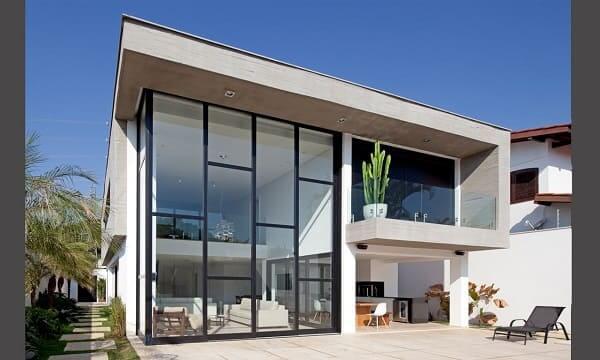 Casa quadrada: ampla janela de vidro traz integração com área externa (projeto: Fabiana Freire)