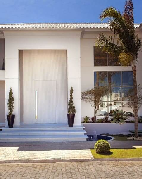 Casa quadrada: fachada branca com janela de vidro e porta pivotante (projeto: Iara Kilaris)