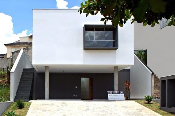 Casas quadradas modernas pequenas: fachada branca com janela preta e pilotis (projeto: Cezar Augusto Pires)