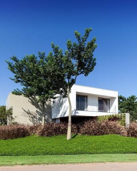 Casa quadrada: fachada branca integrada com a natureza (projeto: Consuelo Jorge)