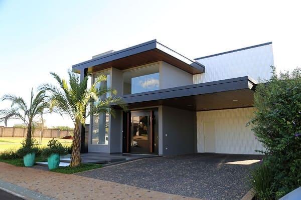 Casa quadrada: fachada com parede de vidro e vasos verdes (projeto: Belezini + Dalmazo Arquitetura)