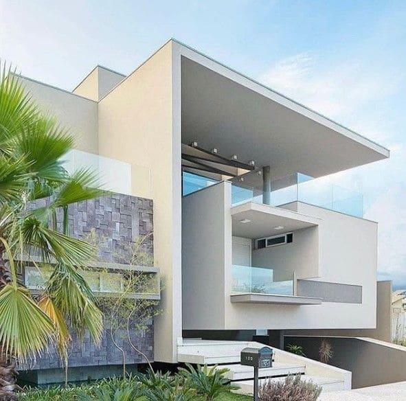 Casa quadrada: fachada com revestimento neutro e escada branca (fonte: Revista Viva Decora)