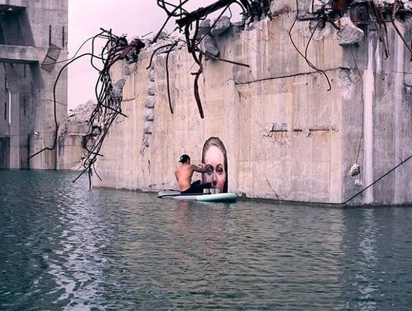 Intervenção Urbana: Sean Yoro pintando o muro sobre a prancha
