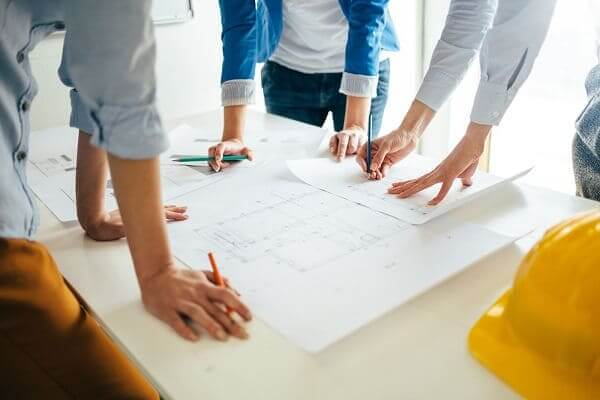 Métricas para escritório de arquitetura: Grupo de profissionais trabalhando em plantas de projeto (fonte: adobestock)
