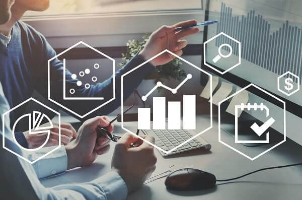 Métricas para escritório de arquitetura: profissionais analisando gráficos no computador e ícones relacionados a métricas (fonte: adobestock)