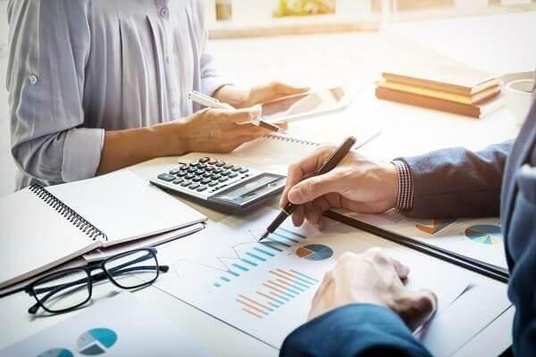 Métricas para escritório de arquitetura: Profissionais realizando análises financeiras a partir de gráficos (fonte: adobestock)