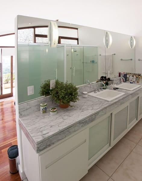 Balcão de mármore cinza e parede com espelho (projeto: C2HA Arquitetos)