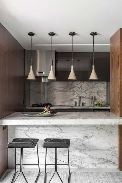 Balcão de mármore em cozinha americana fica elegante em decoração preta e branca