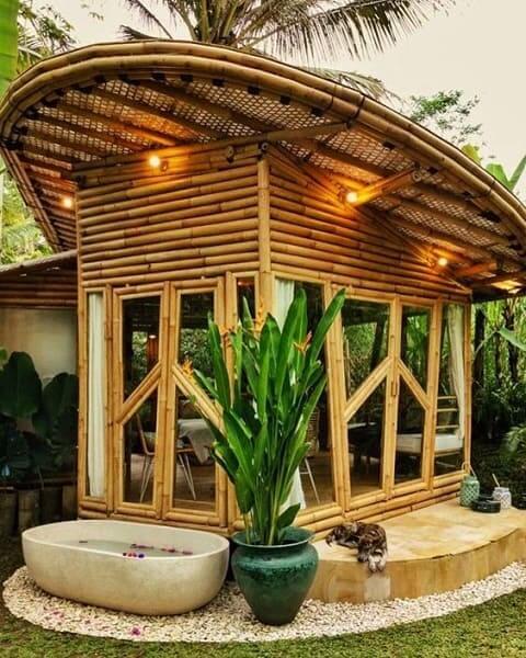Casa de bambu: chalé com porta de vidro e iluminação na cobertura
