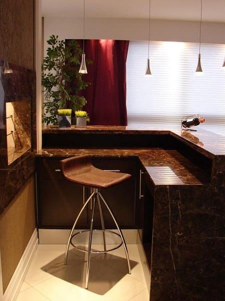 Churrasqueira com balcão de mármore escuro e assento marrom (projeto: Lívia Gobetti)