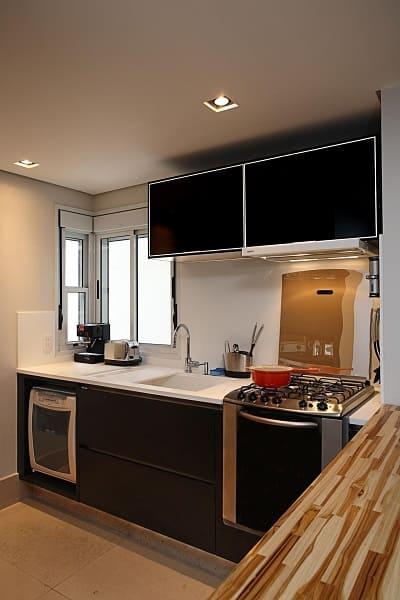 Balcão de mármore branco com gabinete preto e pia (projeto: Karen Pisacane)