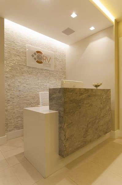 Balcão de mármore em recepção de tons neutros (projeto: Bernal Projetos)