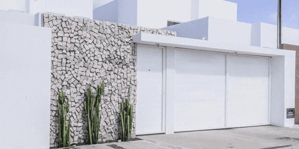 Pedra portuguesa acinzentada na fachada combina com portão branco
