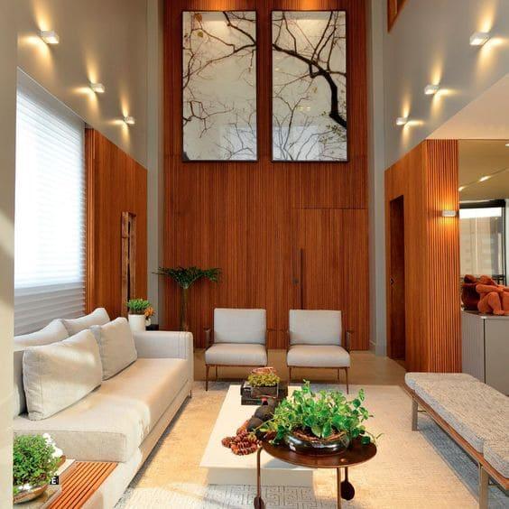 6. Pé direito duplo quadro de árvore e painel de madeira traz clima de natureza para o espaço