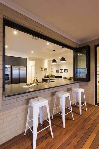 Passa prato com janela, balcão preto e bancos brancos (foto: Pinterest)