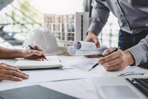 Problemas na gestão de obra: profissionais trabalhando sobre a mesa com projetos de construção civil (foto: Adobe Stock)