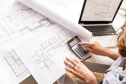 Problemas na gestão de obra: profissional realizando contas sobre planta de projeto (foto: Adobe Stock)