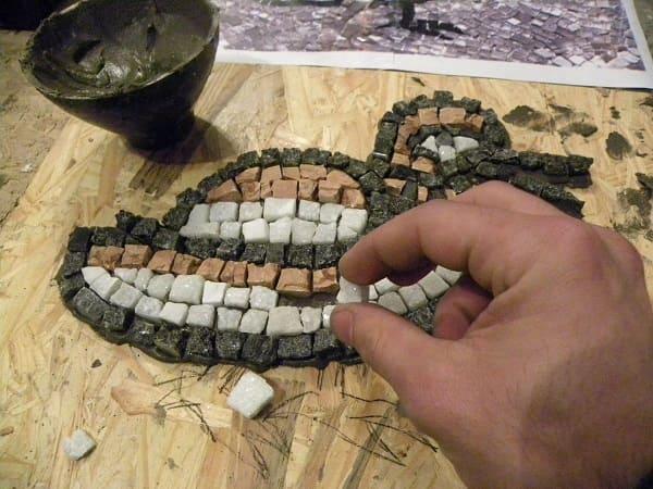 Tesselas de pedra colocada em painel de madeira