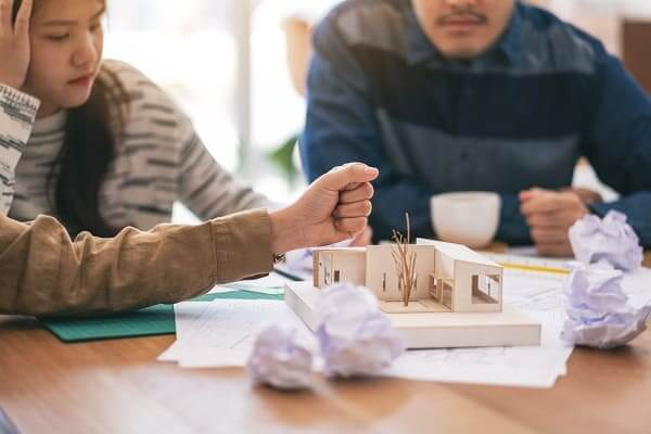 Pré-Obra: Arquitetos trabalhando em um projeto, e em cima da mesa uma maquete (Adobe Stock Photos)