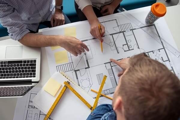Pré-Obra: Profissionais trabalhando juntos sobre planta (Adobe Stock Photo)