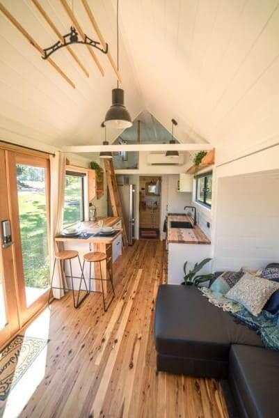 Tiny House com piso de madeira e sofá preto (foto: Pinterest)