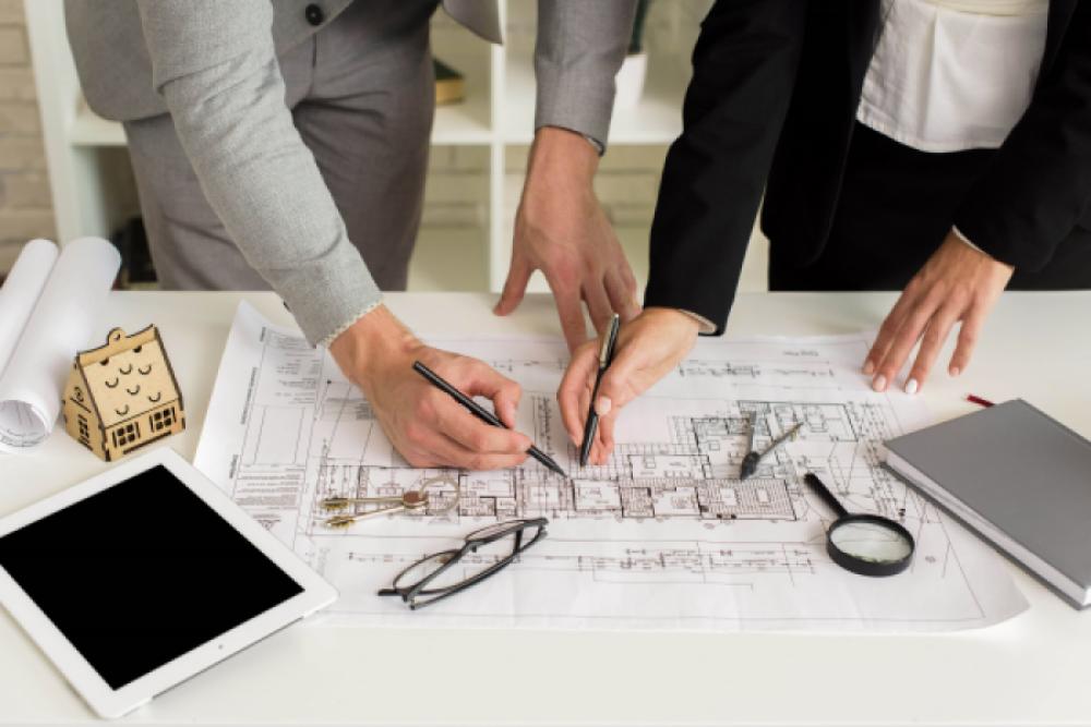 Atrasos na obra: profissionais trabalhando sobre planta de projeto (foto: Adobe Stock)