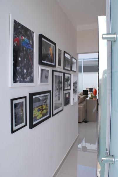 Parede de quadros no corredor com molduras em preto e branco (foto: Projética Design e Arquitetura)