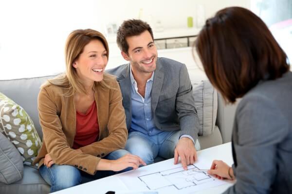 Primeira reunião com o cliente: Profissional e clientes sentados em mesa para discutir o projeto