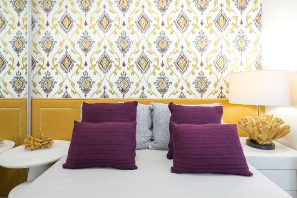 Círculo Cromático: cores complementares - cabeceira amarela e almofadas roxas (foto: Blog de Decoração Lolahome)